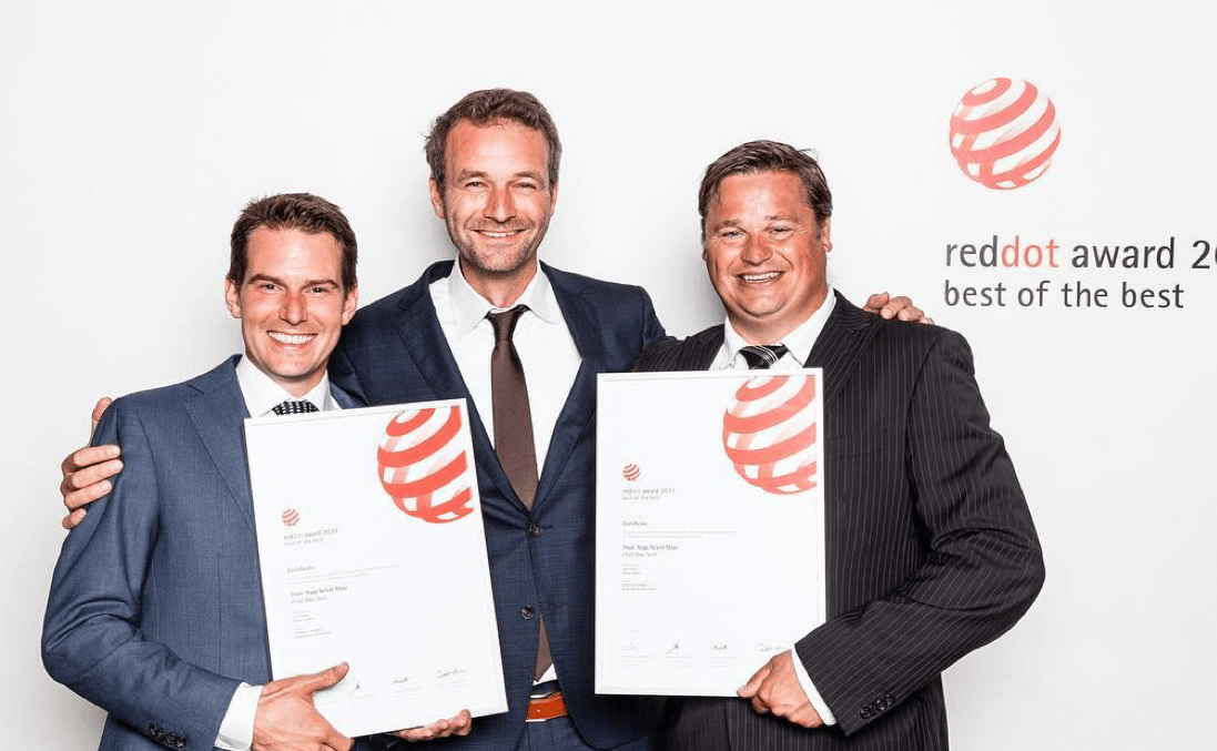 Three men, two holding reddot awards from 2017
